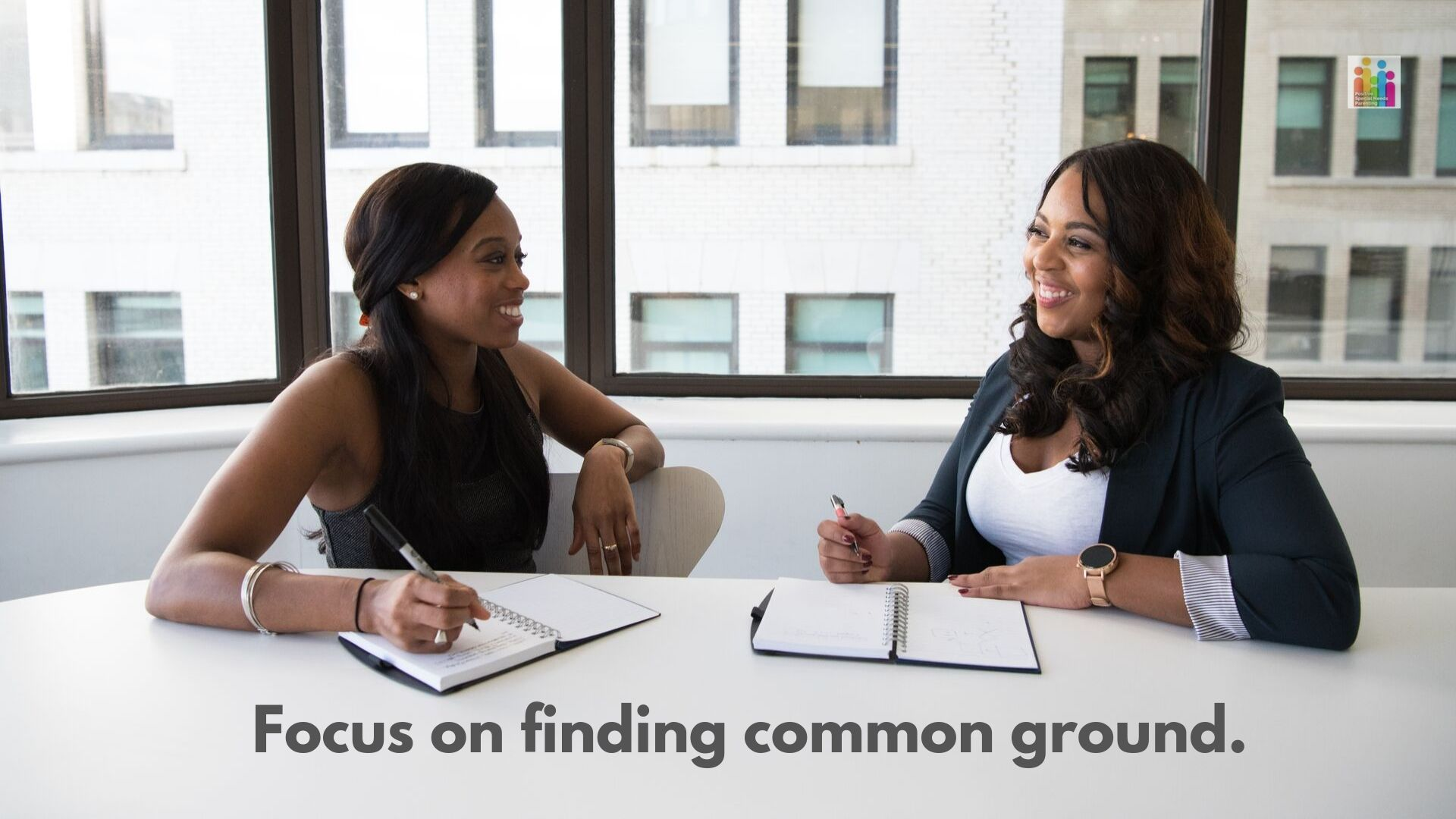 "Image of two African American women, both with dark hair, smiling at each other at a desk. They both have open notebooks in front of them with a pen in their hand with the text ""focus on finding common ground."""