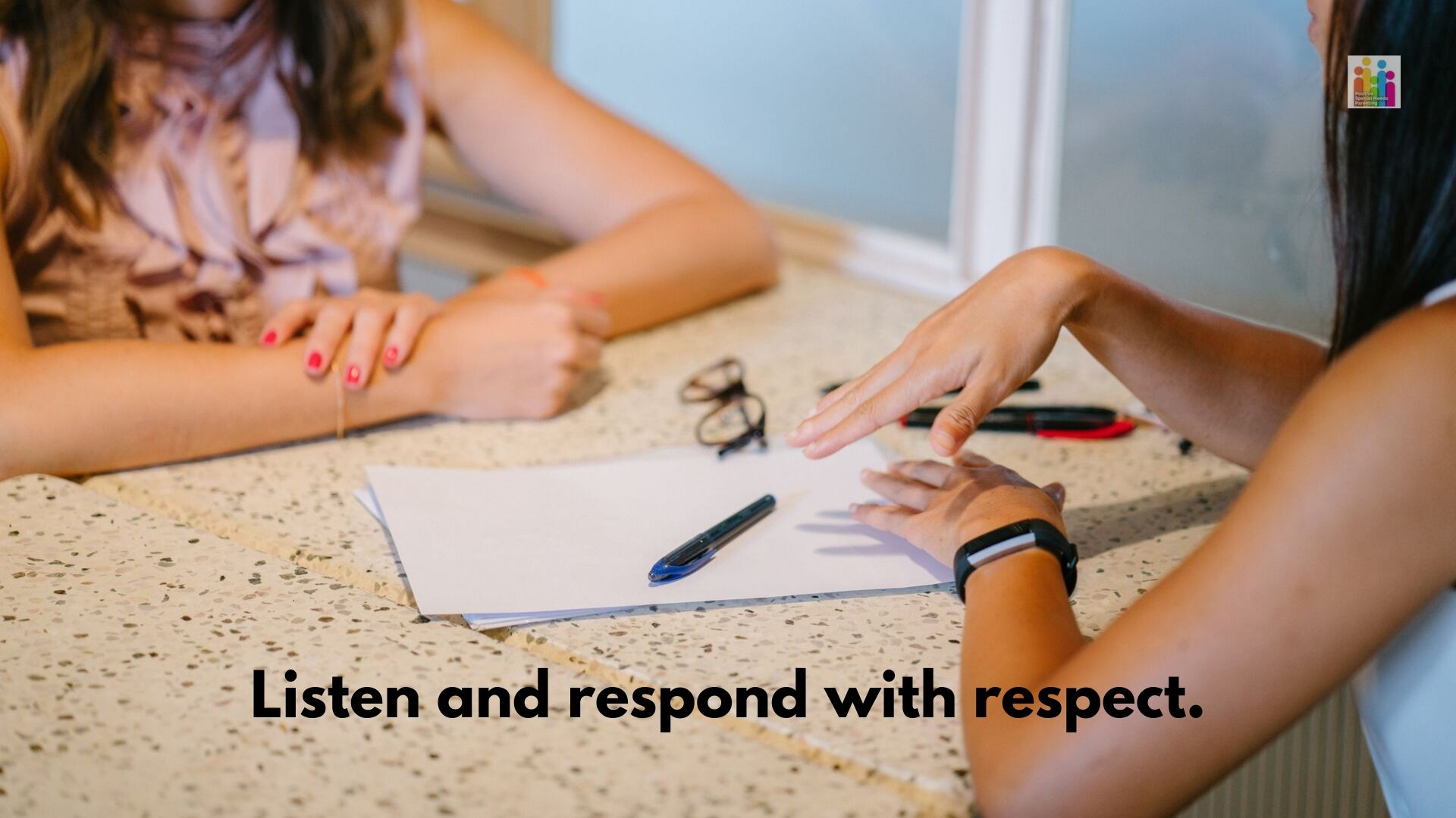 "Close up image of a table with paper, pens and a pair of glasses visible. Two women are sitting on either side of the table, with their arms visible as if in conversation. Text below the image reads, ""listen and respond with respect."""